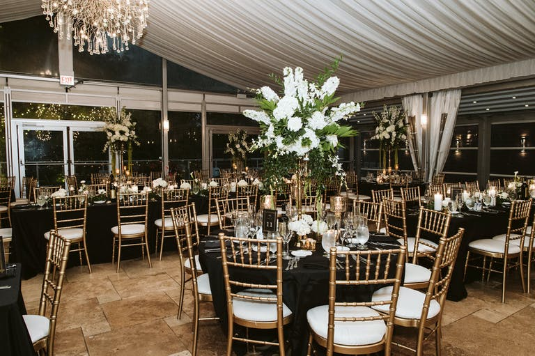 Tented Wedding Reception Venue with Gold Chavari Chairs, Black Linen, and Towering Sputnik-Style Hydrangea Wedding Centerpiece With Greens and Orchids