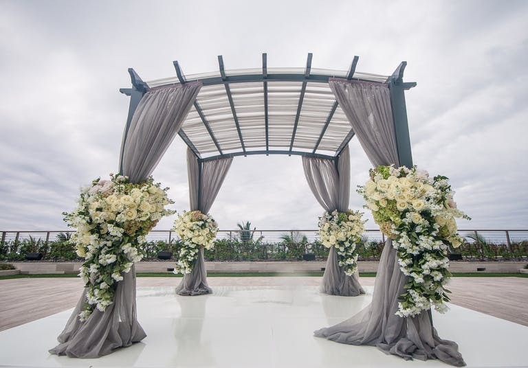 Modern Wedding Arch with Ethereal Gray Drapery and Florals in White and Green Spring Wedding Colors
