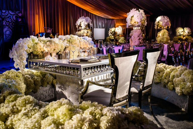Sweetheart Table With with White Orchid and Hydrangea Wedding Centerpieces Surrounded by a Sea of White Hydrangeas