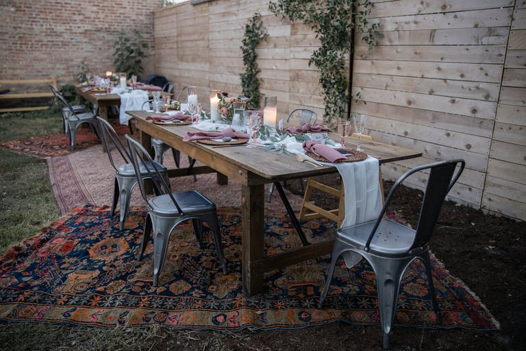 2021 trend sleep wooden kitchen table outside and on top of boho rugs   PartySlate