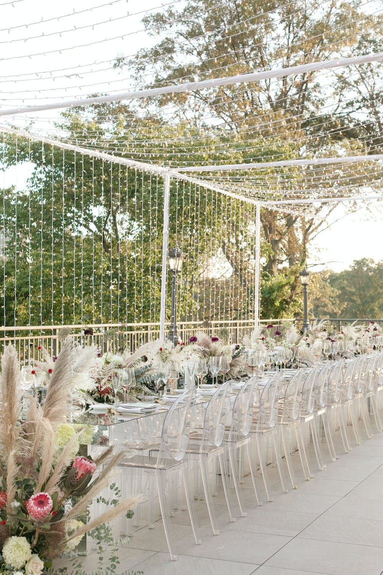 Pampas grass, fall florals and ghost chairs with string lights everywhere | PartySlate