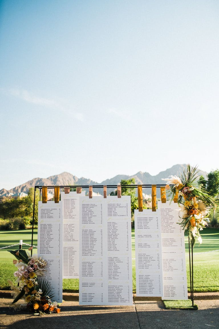 Oversized wooden clips holding up scrolls of seating char | PartySlate