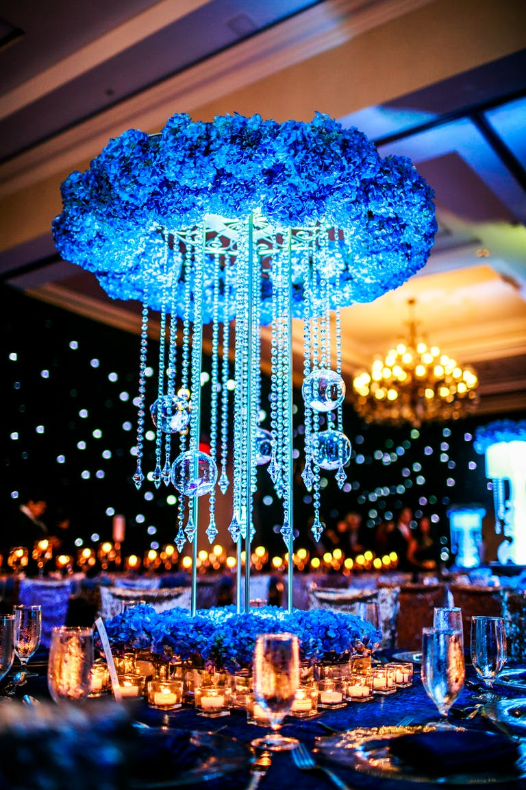 Towering Wedding Centerpiece with Wreath of Blue Hydrangeas and Suspended Crystals and Glass Globes