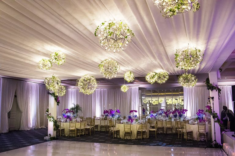 Wedding Reception With Purple Uplighting and Spring Greenery Lighting Fixtures