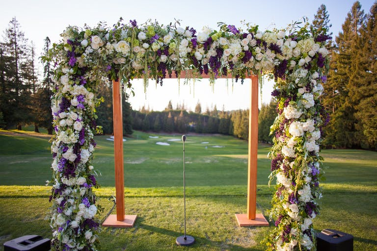 Wooden Wedding Arch with Florals in White, Green, and Purple Spring Wedding Colors