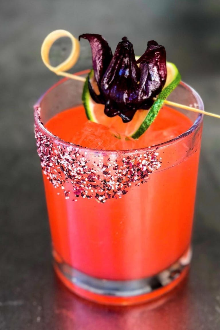 Reddish-Orange Cocktail by Wolfgang Puck Catering With Dried Hibiscus and Cucumber Garnish | PartySlate