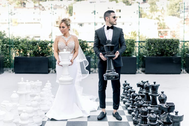 Bride and Groom Pose With Larger than Life Chess Board | PartySlate