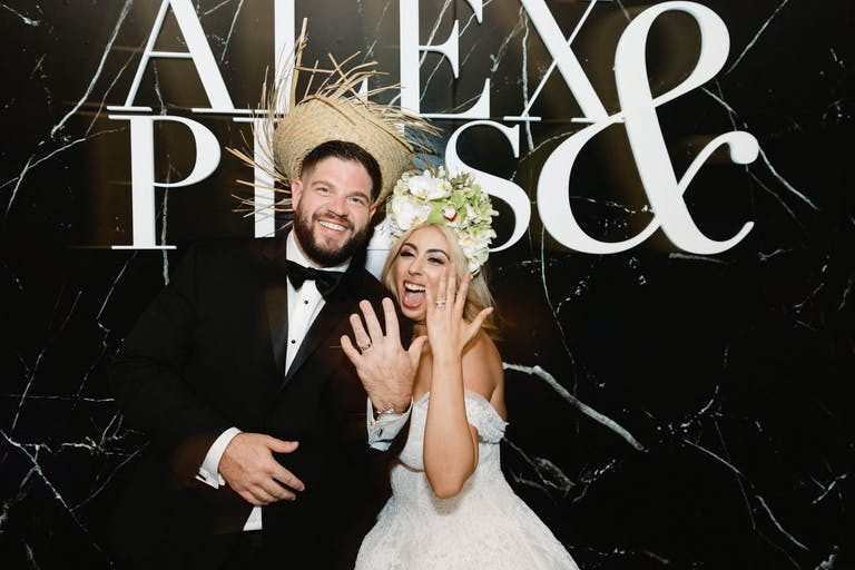 Bride and Groom Show Off Rings in Front of Marbled Black and White Backdrop With Their Names | PartySlate