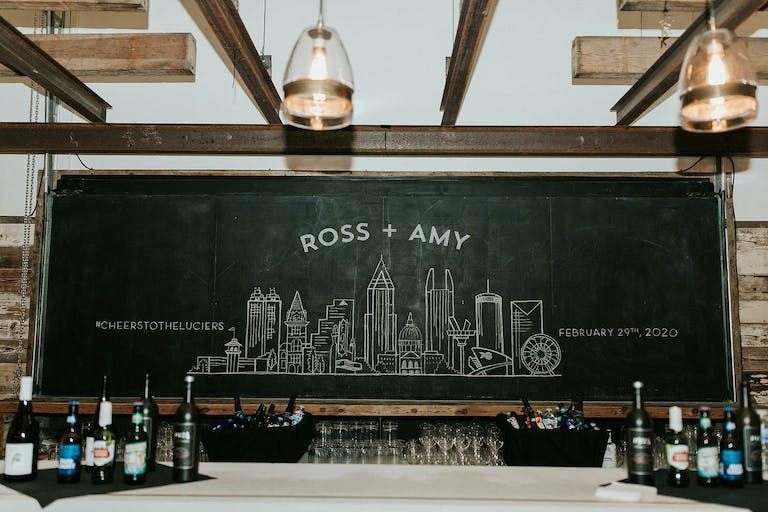 Wedding With Chalkboard Signage that Features City Scape and Couples Names | PartySlate