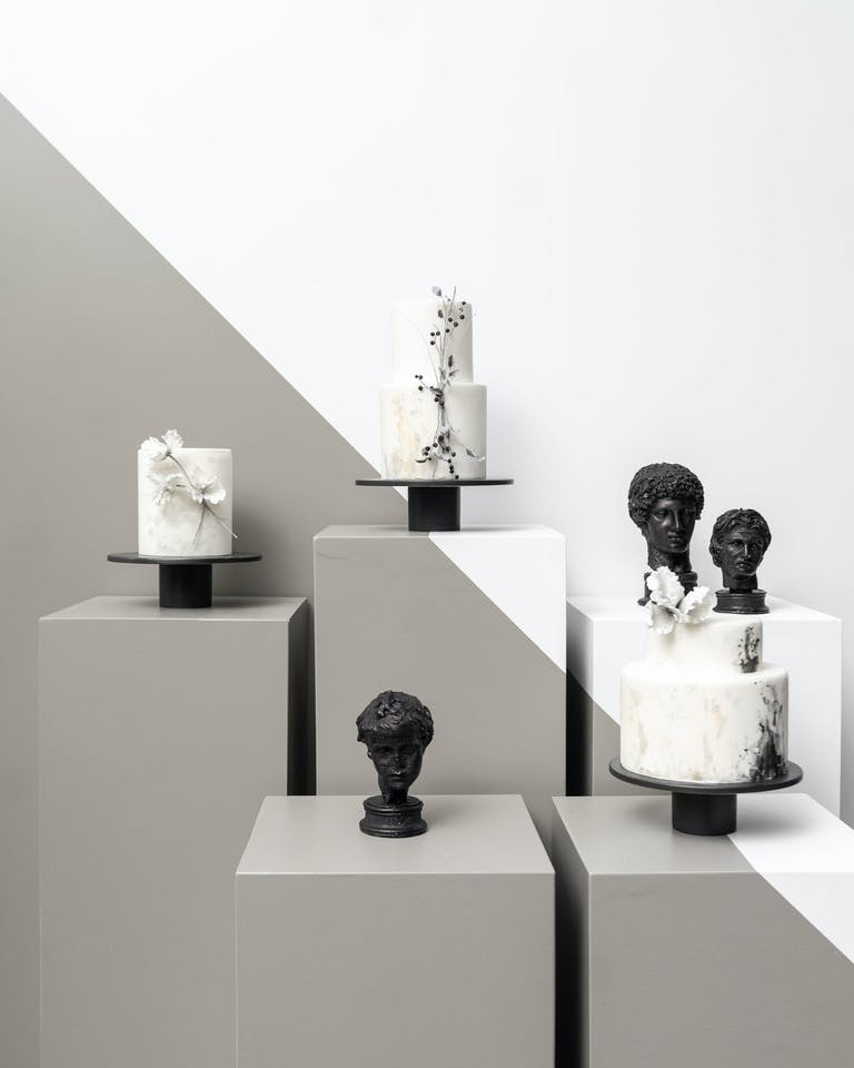 Three Black and White Wedding Cakes with on Gallery-Like Display With Black Statue Heads | PartySlate