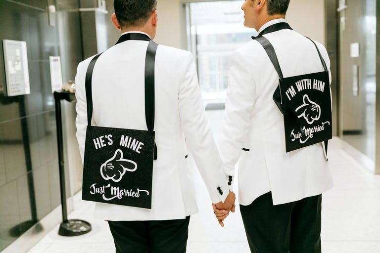 Two Grooms Wear Just Married Signs in Black and White Wedding Colors | PartySlate