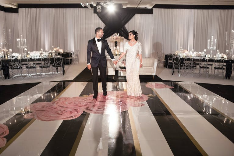 Couple Poses on Black and White Dance Floor With Pink Roses | PartySlate