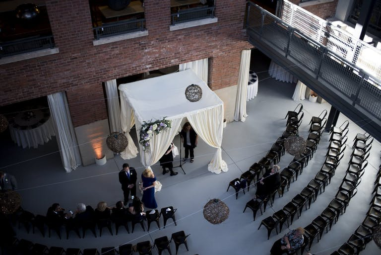 White Wedding Chuppah and Black Ceremonial Seating Against an Industrial Brick Wall | PartySlate
