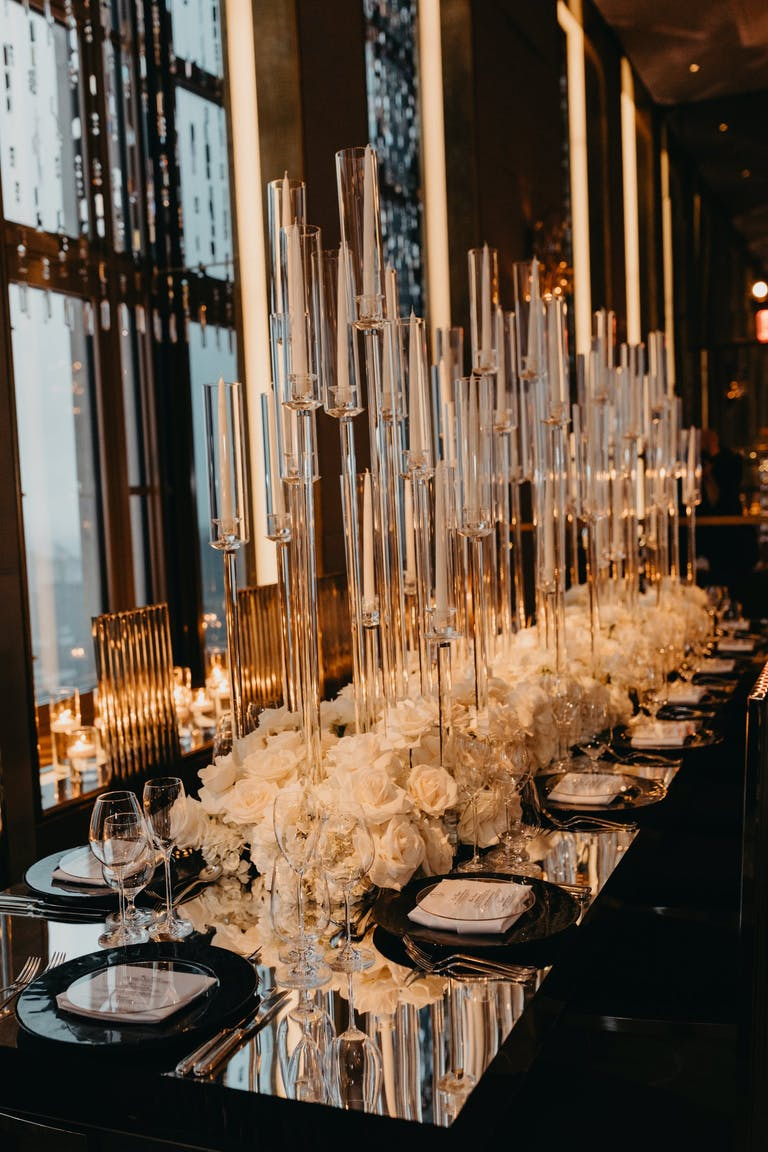 Black and White Wedding Tablescape With Towering Candles, Mirrored Tabletops, White Rose Centerpieces, and Black Dinnerware | PartySlate