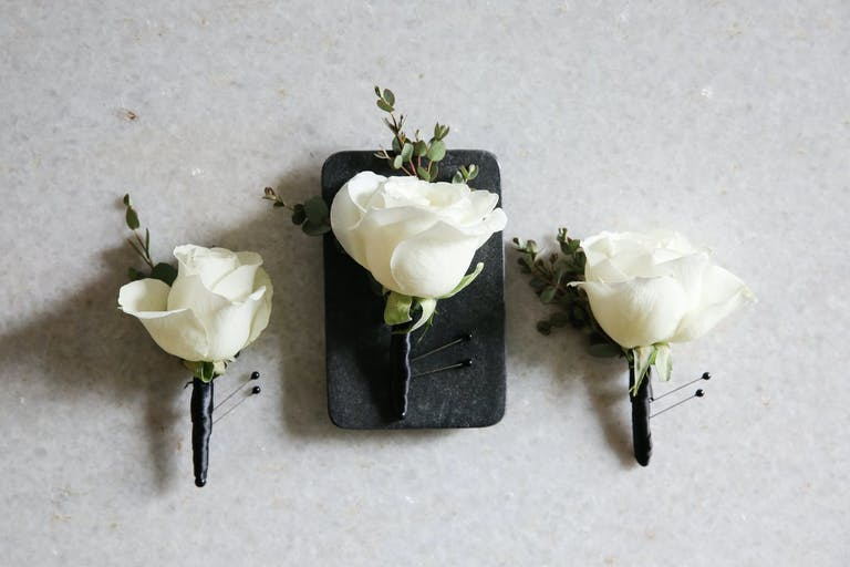White Rose Boutonnières with Stems Wound in Black Ribbon | PartySlate