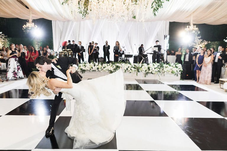 Couple Kisses Mid Dance on Black and White Checkered Dance Floor | PartySlate