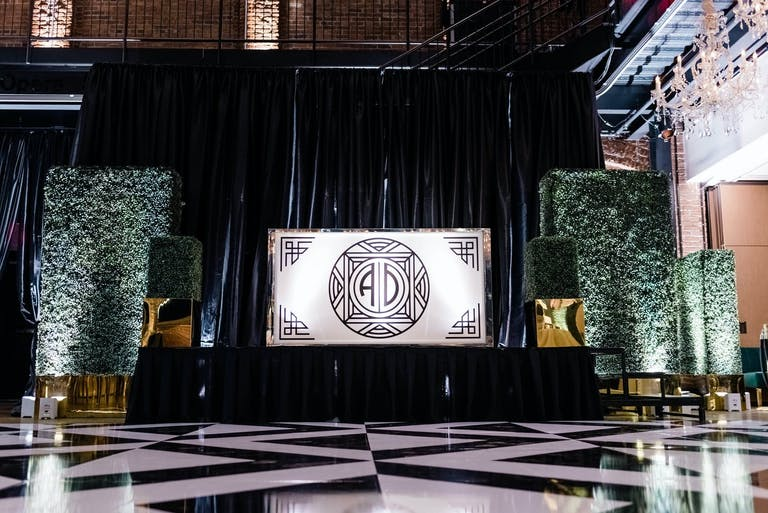 Black and White Wedding With Art Deco Dance Floor and Backdrop as Well as Boxwood Décor | PartySlate