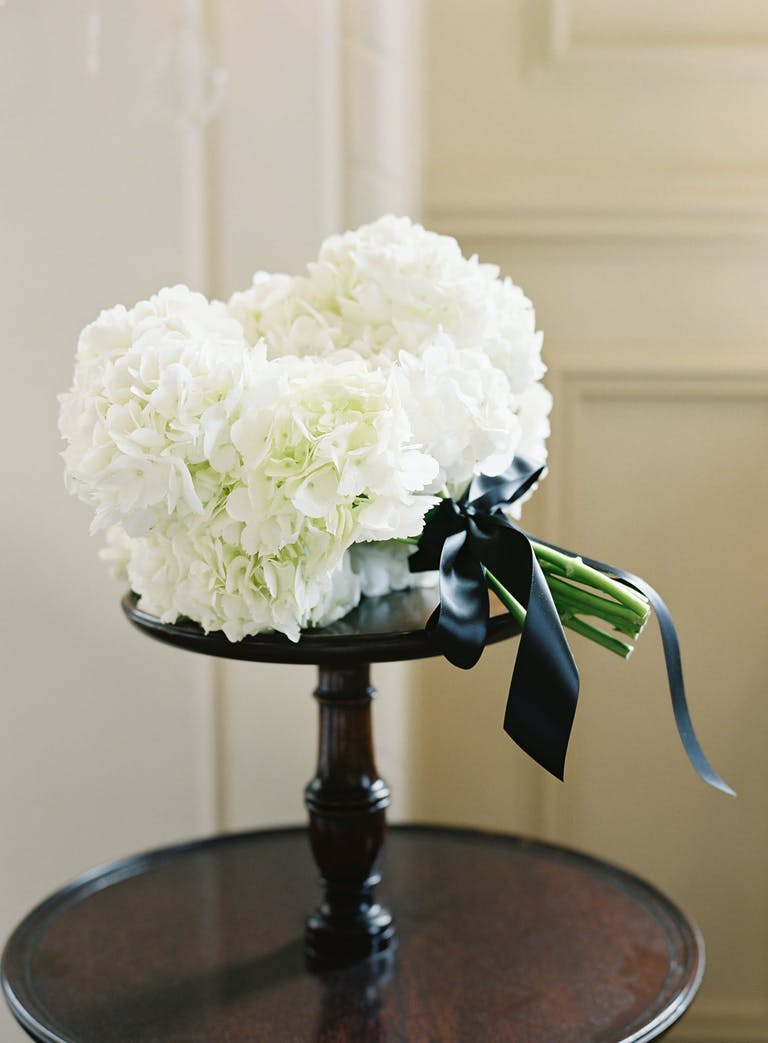 White Hydrangea Wedding Bouquet With Black Bow | PartySlate
