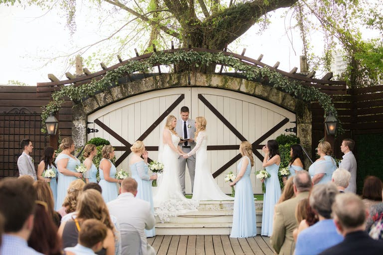 Two Brides Exchange Vows at Hughes Manor in Houston, Texas With Rustic Barn Doors in Backdrop | PartySlate