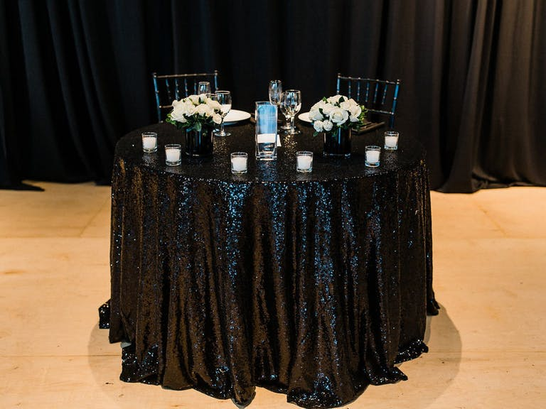 Wedding Sweetheart Table With Glittery Black Linen and White Flowers | PartySlate