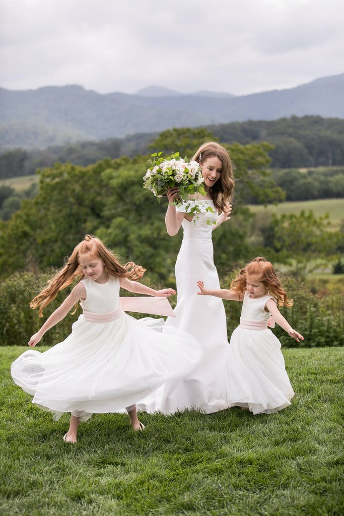 Bride Spins With Two Flower Girls on Hilltop | PartySlate
