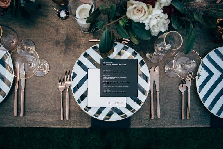 Black and white striped plate design with gold utensils for a modern wedding   PartySlate