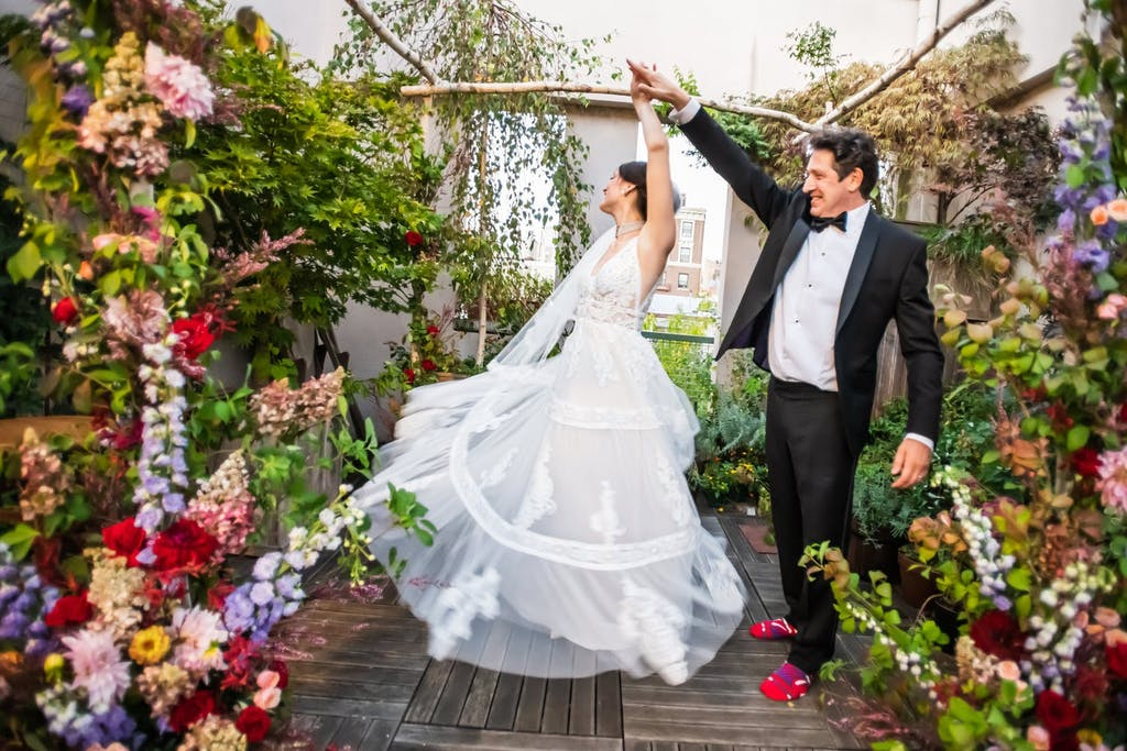 Bride and Groom Dance Under an Arbor Surrounded by Colorful Flowers | PartySlate