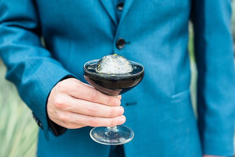 Man in Blue Jacket Holds a Modern Black Cocktail at Wedding   PartySlate