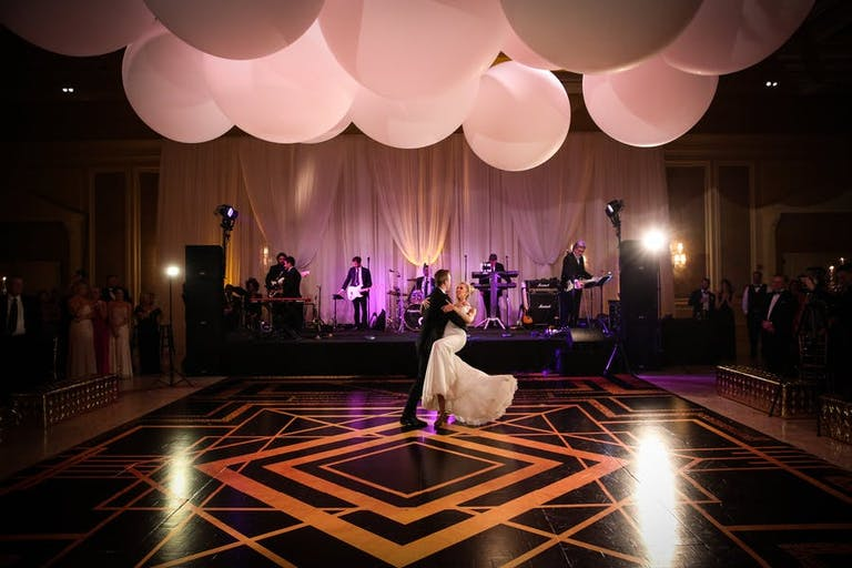 Deco designed gold and black wedding dance floor | PartySlate