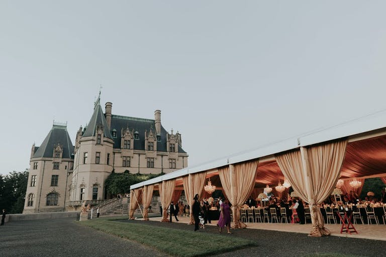 Gold wedding tent next to castle like building | PartySlate