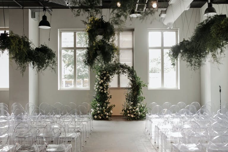 Modern wedding with green arches and draping greenery   PartySlate