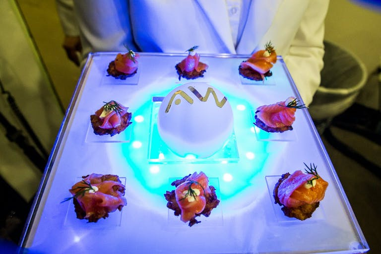 Man Hold Tray of Small Bites on Neon Tray   PartySlate