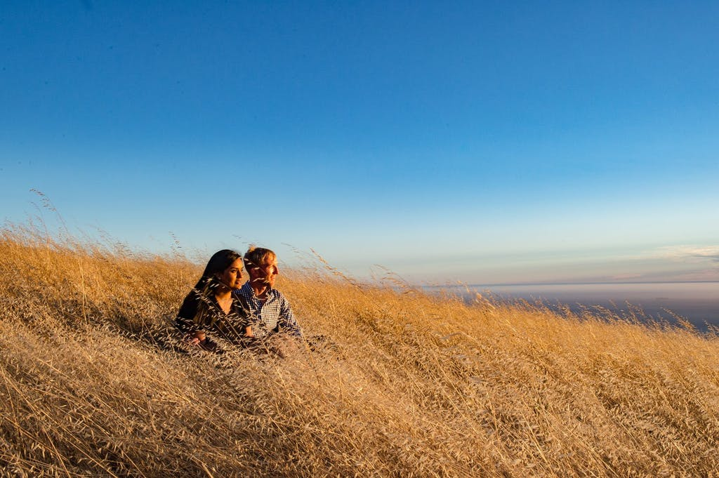 Engaged Couple Sit in Golden Field Under Deep Blue Sky | PartySlate