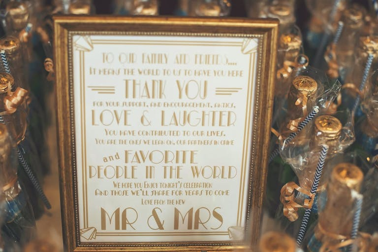 Deco Gatsby theme signage with mini champagne bottles | PartySlate