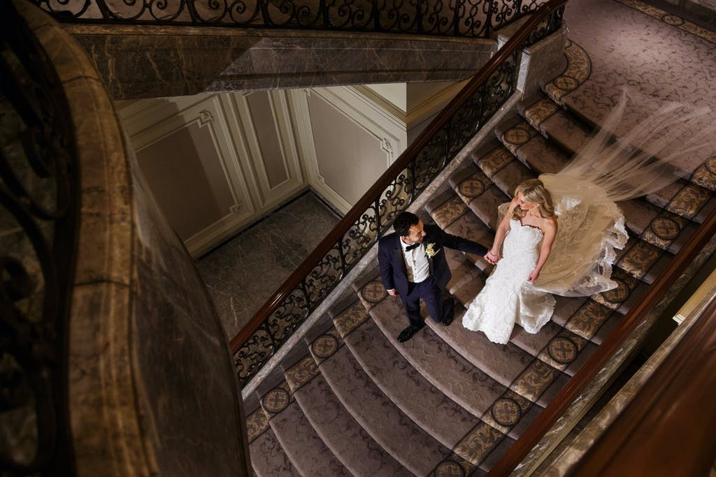 Groom Lead Bride Walking Down Stairs | PartySlate