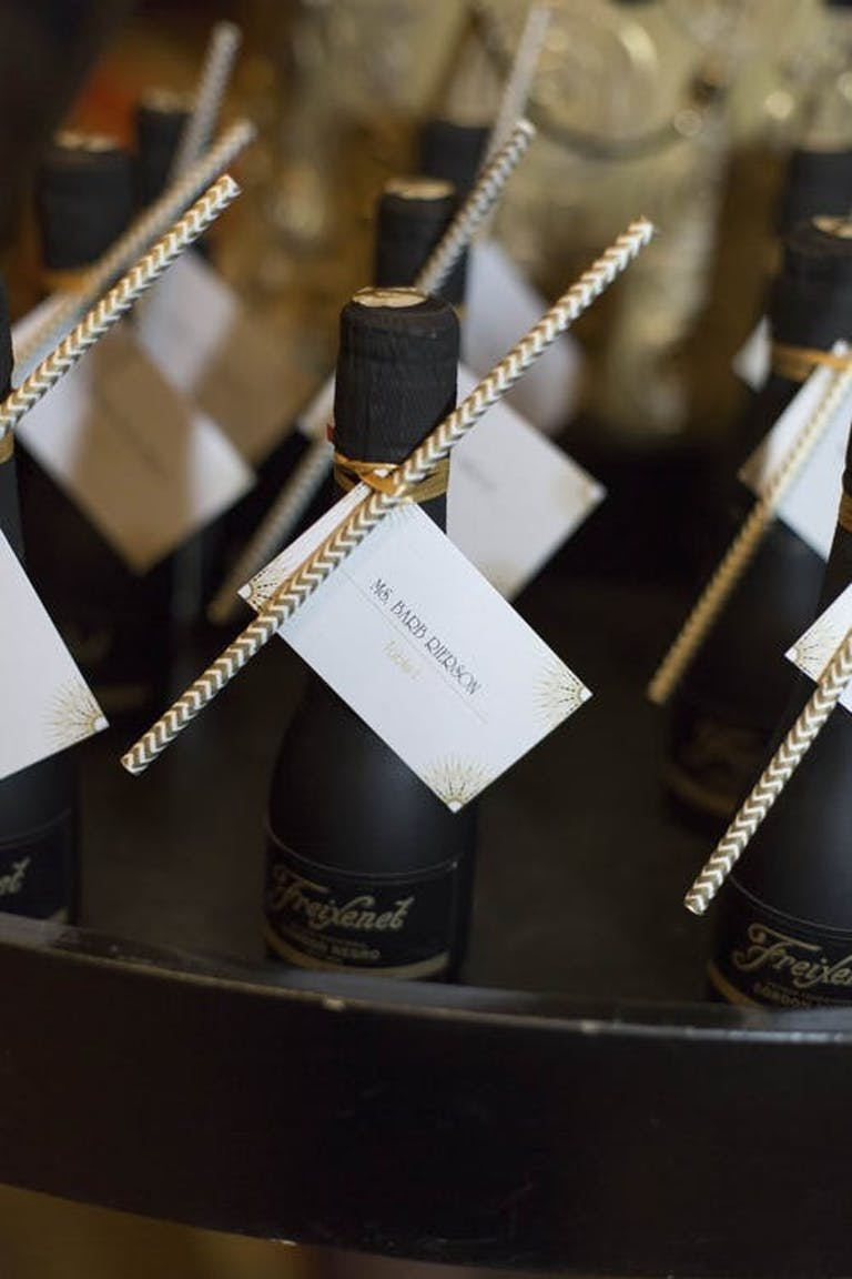 Mini black champagne bottles with table numbers | PartySlate
