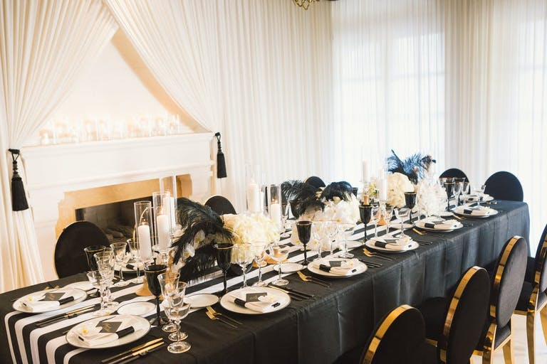 Black and white lined table with gold detail and black and white feathers, Gatsby theme | PartySlate