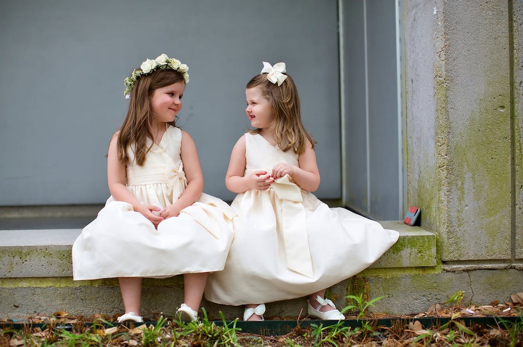 Two Flower Girls Smile at Each Other | PartySlate