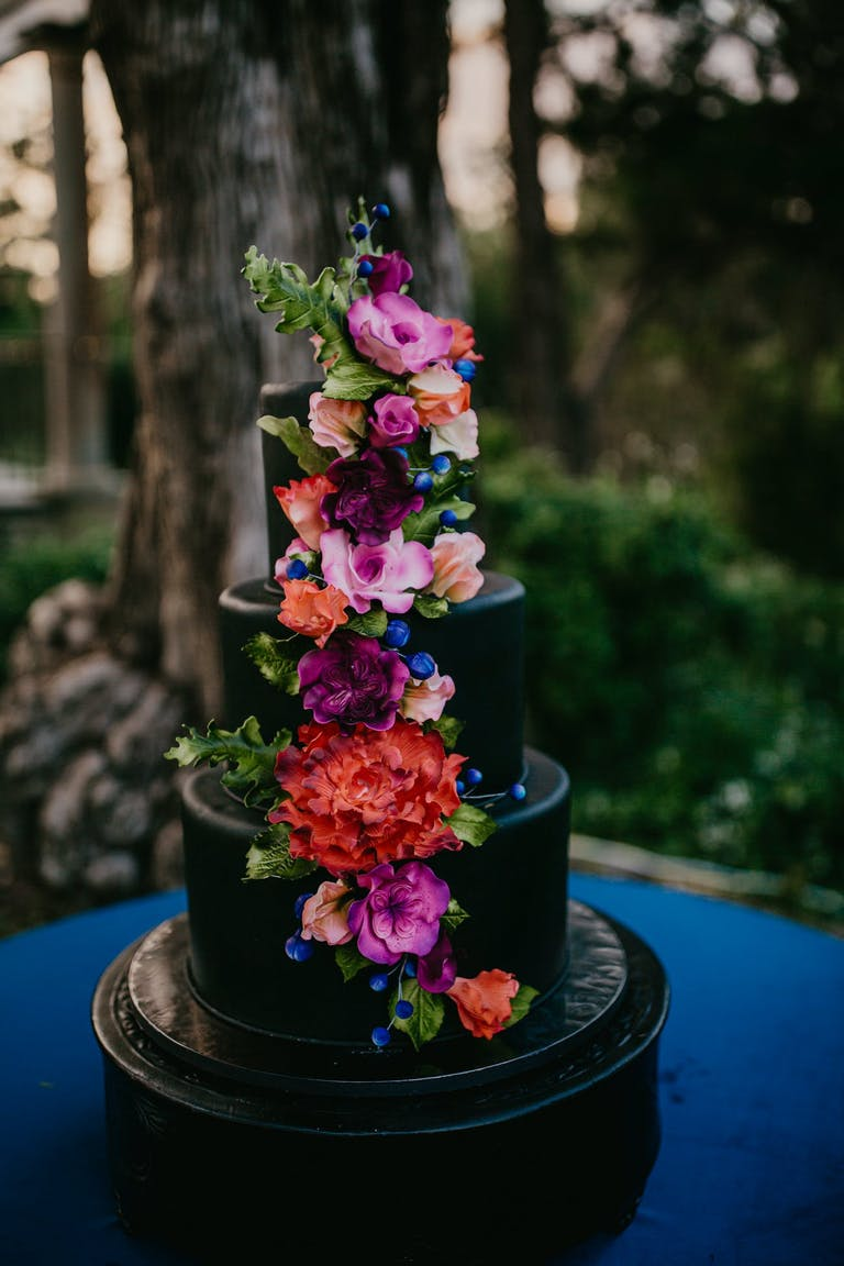 Black tiered cake with bright florals modern wedding   PartySlate