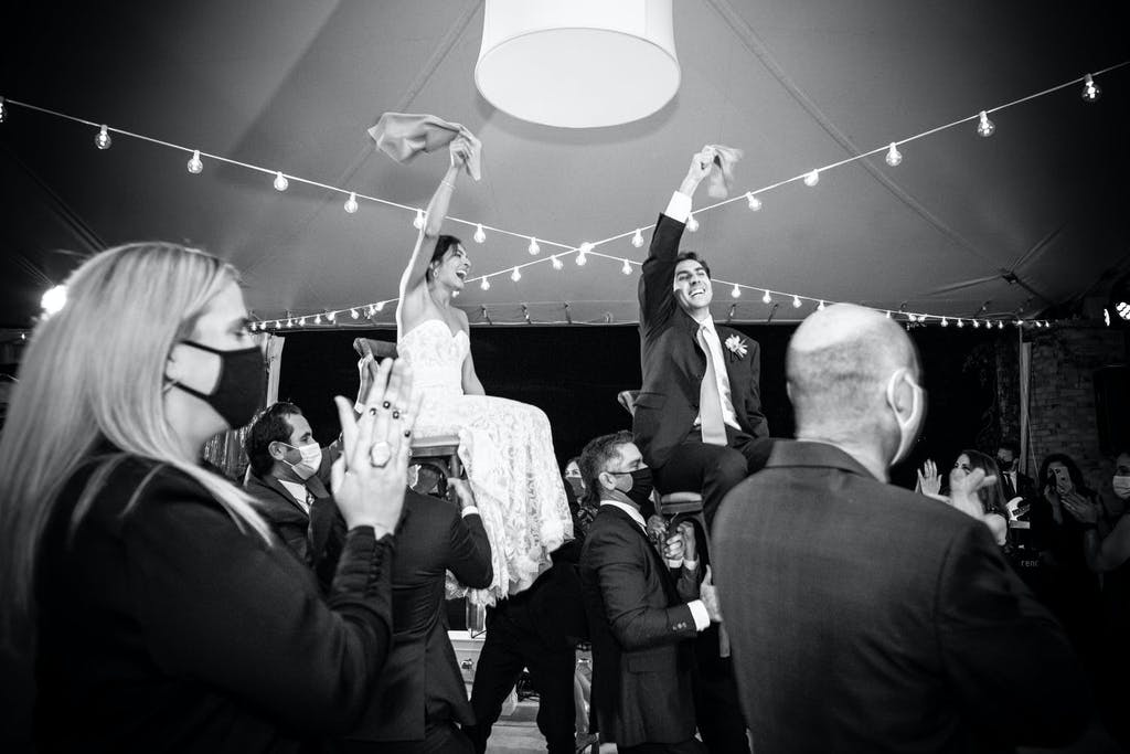 A Woman and Man Wear Masks as The Bride and Groom Are Raised on Chairs During the Horah | PartySlate