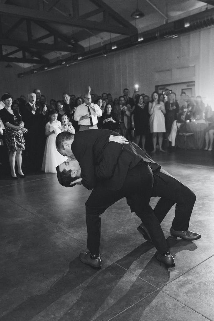 Two Grooms Kiss on Dance Floor While Surrounded by Friends | PartySlate