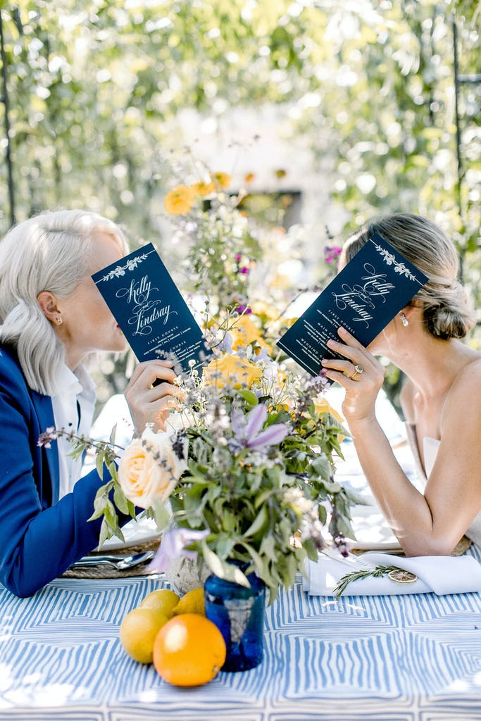 Bride and a Friend Have Private Conversation Behind Two Menus | PartySlate