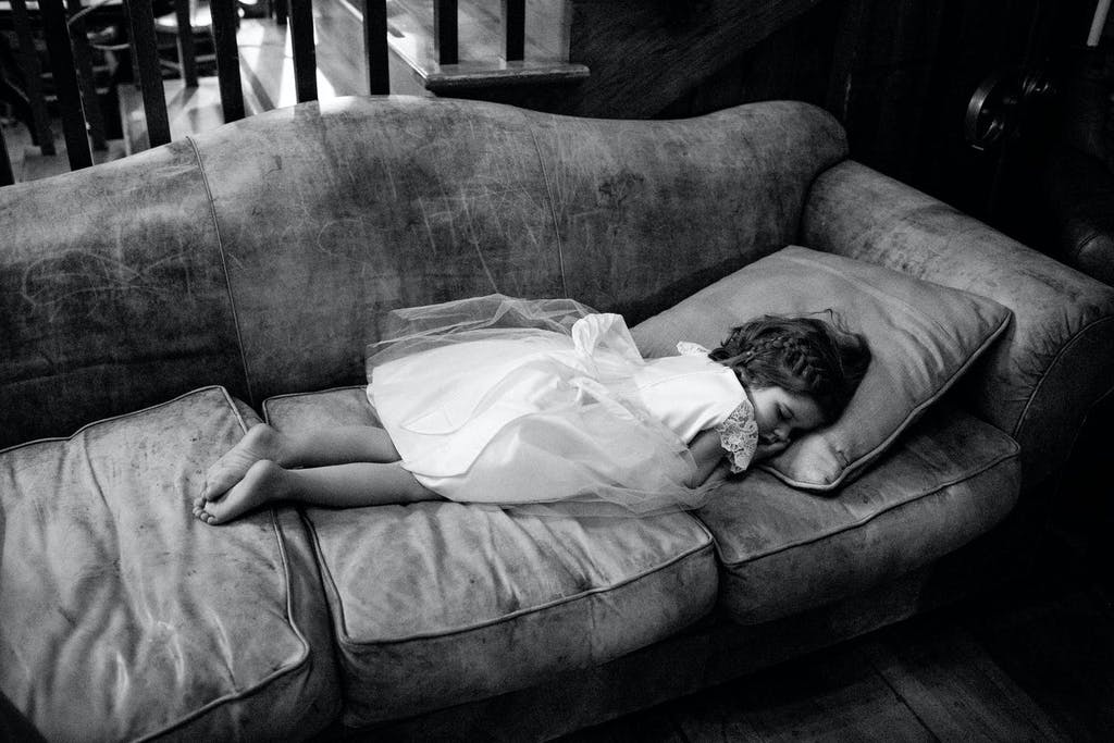 Little Girl in White Party Dress Sleeps on Sofa | PartySlate
