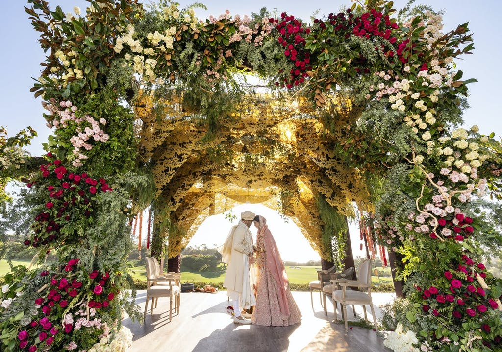 Bride and Groom Touch Foreheads Under a Lavish Floral Mandap | PartySlate