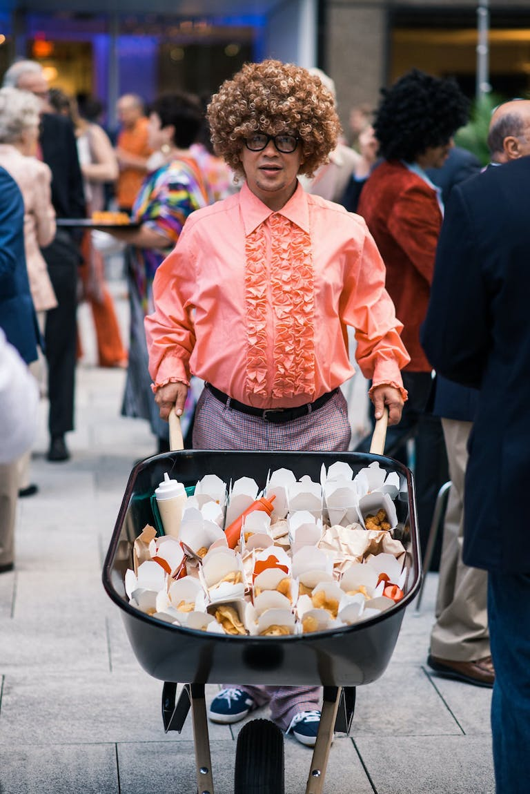 1970'S CALIFORNIA POOLSIDE-THEMED ANNIVERSARY PARTY With Man in Salmon-Color Ruffled Shirt Pushing Wheel Barrow Filled With Ramen Catering | PartySlate