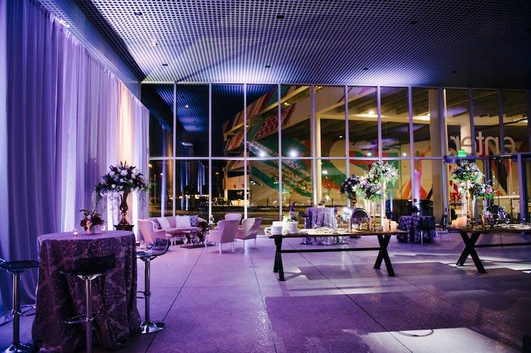Vibrant purple uplighting for a modern wedding display   PartySlate