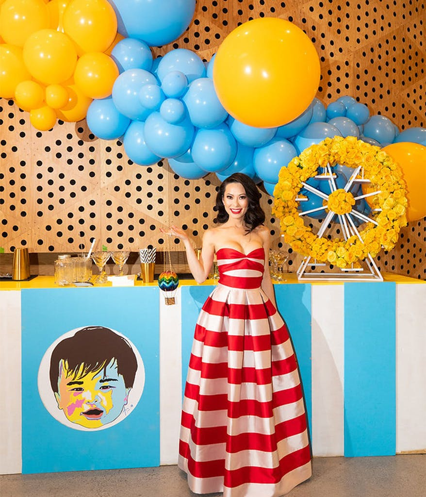 mom at her son's first birthday party wearing a red and white striped dress with yellow and blue balloons