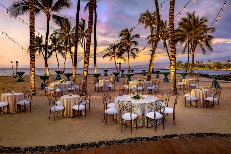 Wedding reception set in sand under palm trees | PartySlate