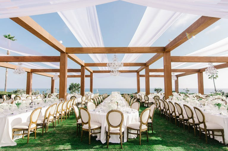 Outdoor beach wedding venue with turf and white linen draping | PartySlate