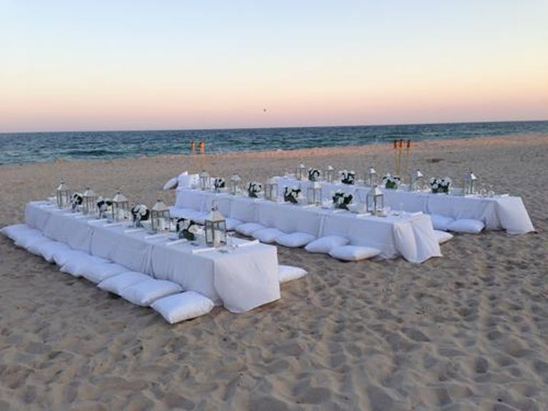 Beach wedding dinner with white linens and white cushions | PartySlate